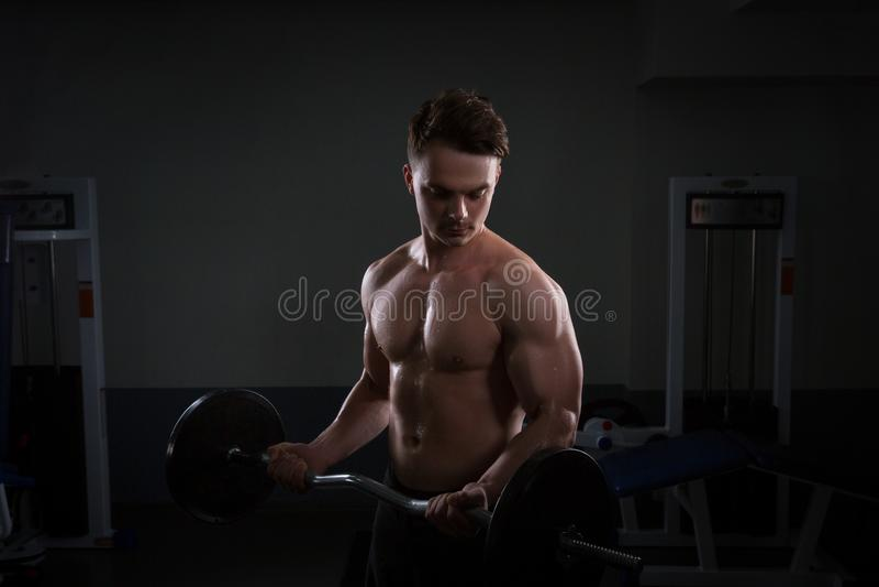 Fermez-vous des poids de levage de jeune homme musculaire au-dessus du fond foncé image stock