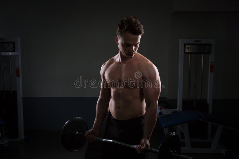 Fermez-vous des poids de levage de jeune homme musculaire au-dessus du fond foncé photos libres de droits