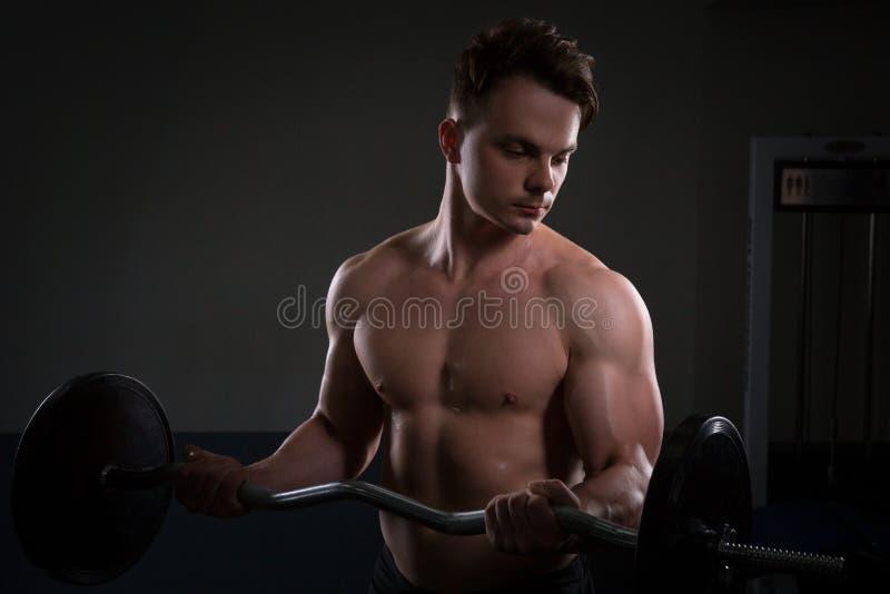 Fermez-vous des poids de levage de jeune homme musculaire au-dessus du fond foncé photographie stock libre de droits