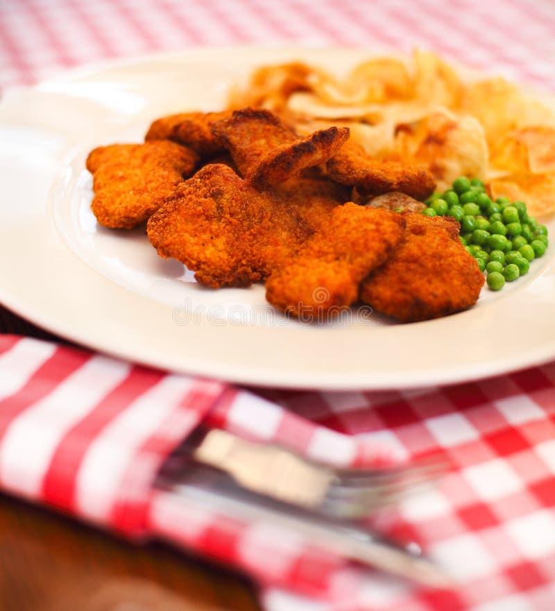 Fermez-vous des poisson-frites avec des pois et d'une tranche de citron photographie stock