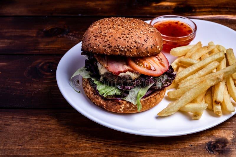 Fermez-vous des pommes frites en soutenant le papier avec les hamburgers faits maison frais, servi avec le pot de sauce à ketchup images stock