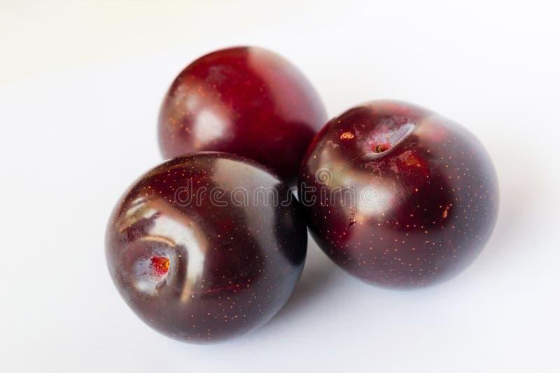 Fermez-vous des prunes de cerise rouges d'isolement photos libres de droits