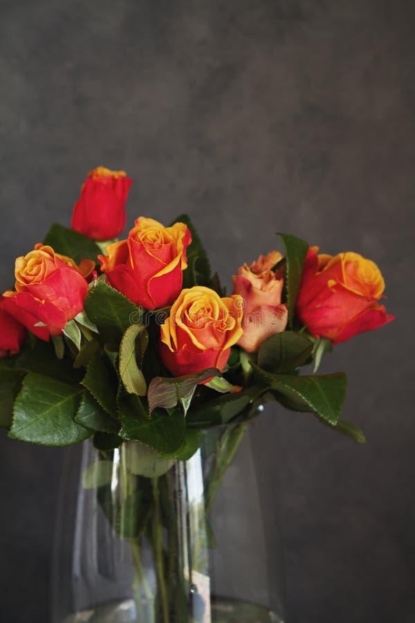 Fermez-vous des roses oranges et jaunes dans le vase en verre photos stock