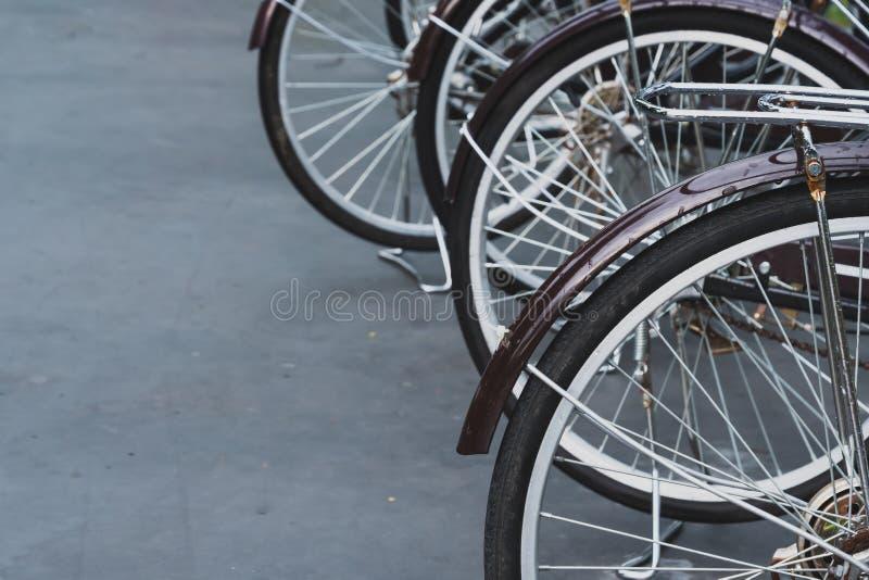 Fermez-vous des roues de bicyclette antiques brunes foncées garées dans les rangées images libres de droits