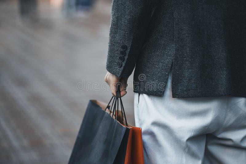 Fermez-vous des sacs à provisions de papier dans la main masculine images stock