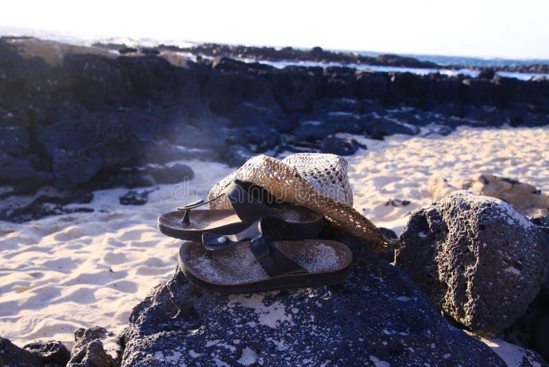 Fermez-vous des sandales avec le chapeau du soleil de paille sur la plage de roche - EL Cotillo, Fuerteventura photographie stock