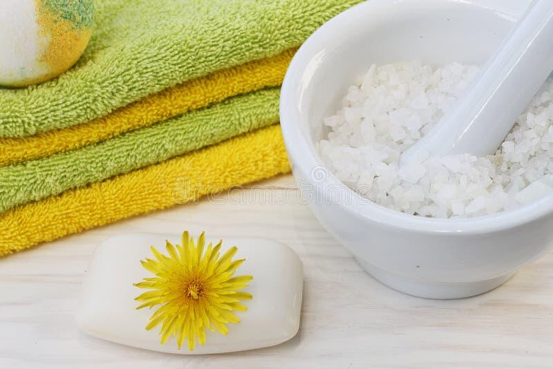 Fermez-vous des serviettes, du savon, de la bombe de bain et du sel de mer sur le fond en bois blanc avec des fleurs de pissenlit images libres de droits