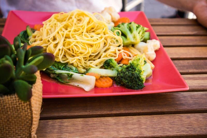 Fermez-vous des spaghetti savoureux avec beaucoup de légumes du plat rose lumineux, pâtes italiennes délicieuses sur la table en  photo stock