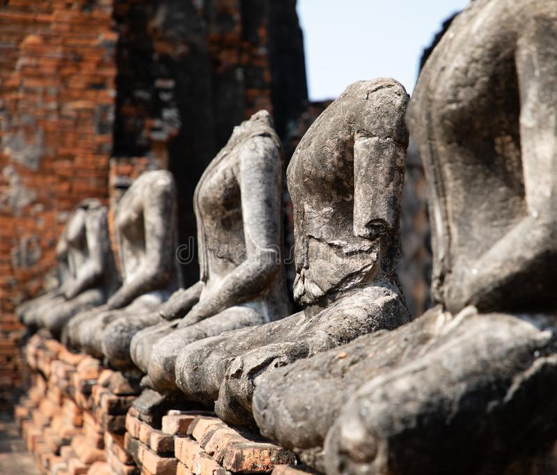 Fermez-vous des statues antiques de Bouddha de pierre placées dans la ligne dans le temple ruiné à Ayutthaya photo stock