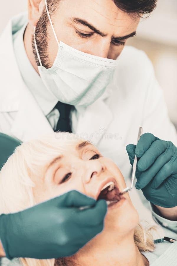 Fermez-vous des stomatologis vérifiant des dents de dame pluse âgé image stock