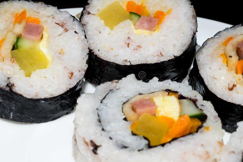 Fermez-vous des sushi roulés de riz d'un plat blanc disposé sur semi une forme de cercle photographie stock libre de droits