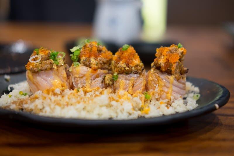 Fermez-vous des sushi saumonés de petit pain de gril sur le plat noir photos stock