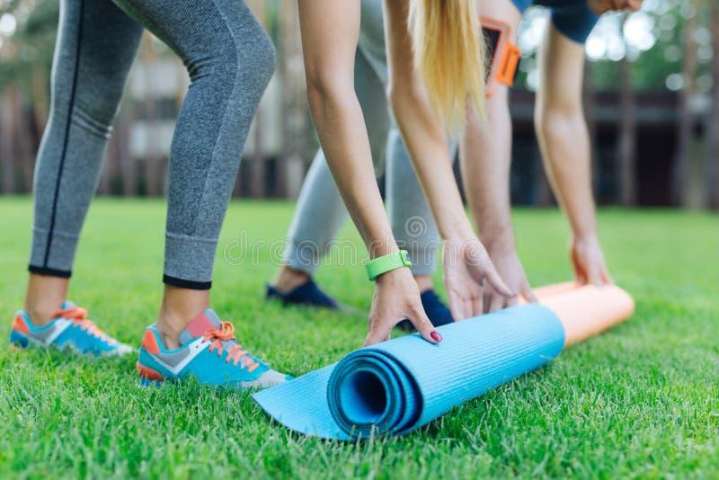 Fermez-vous des tapis de yoga étant mis sur l'herbe photographie stock