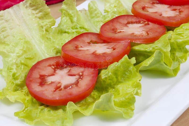 Fermez-vous des tomates et de la laitue coupées en tranches image stock