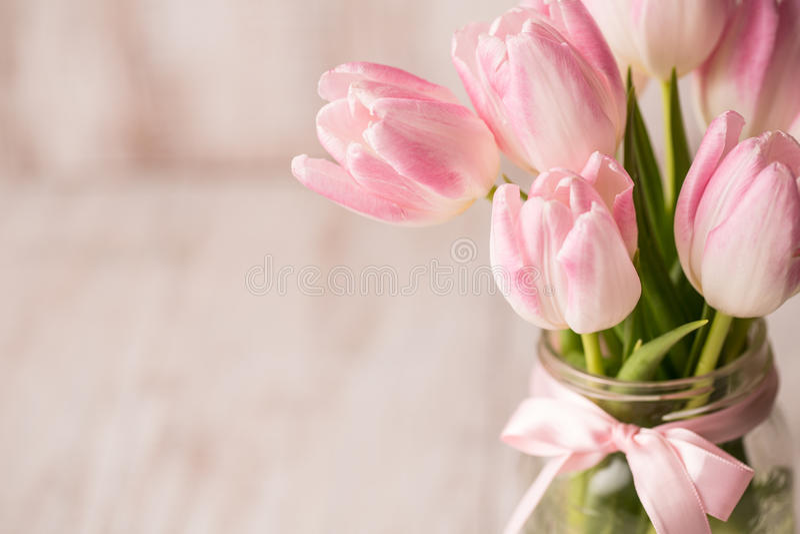 Fermez-vous des tulipes en pastel roses et blanches dans le vase en verre à pot avec image libre de droits