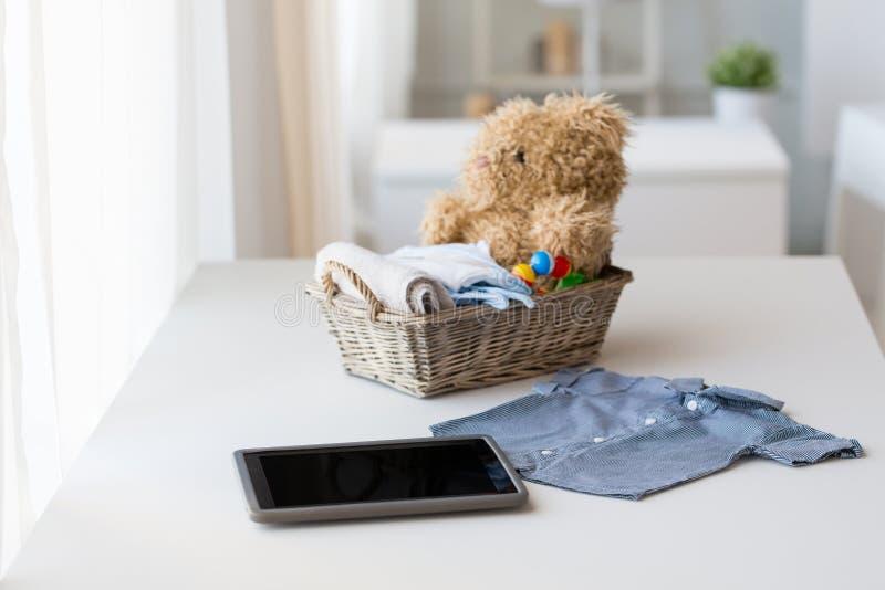 Fermez-vous des vêtements de bébé, des jouets et du PC de comprimé images stock
