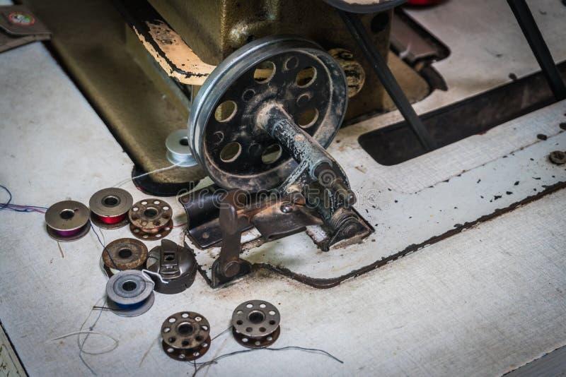 Fermez-vous des vieilles bobines de machine à coudre sur la table de travail Table de travail du ` s de tailleur textile ou fabri image libre de droits