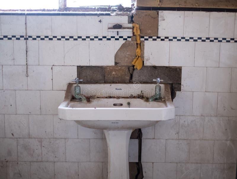 Fermez-vous du bassin de main de jambes et des tuiles originales dans la maison abandonnée de style de deco La Chambre est due po photographie stock