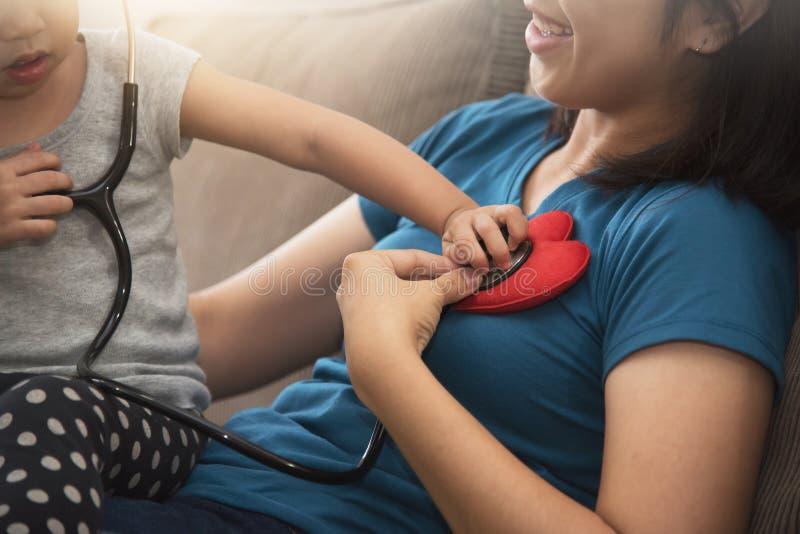 Fermez-vous du battement de coeur de examen de fille asiatique de petit enfant images stock