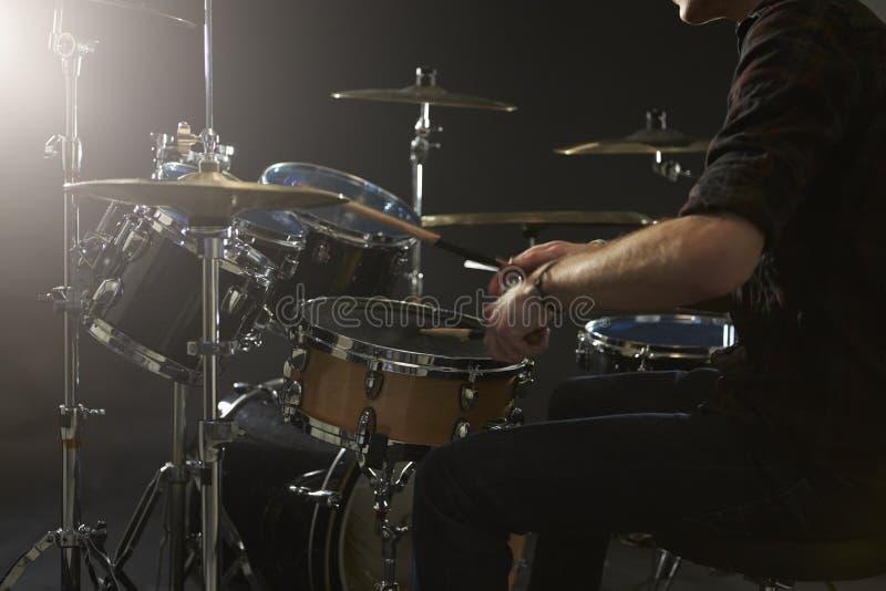 Fermez-vous du batteur Playing Drum Kit In Studio photo stock