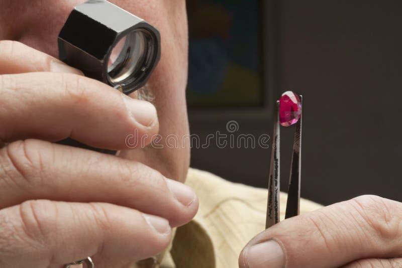 Fermez-vous du bijoutier masculin regardant la pierre gemme image libre de droits