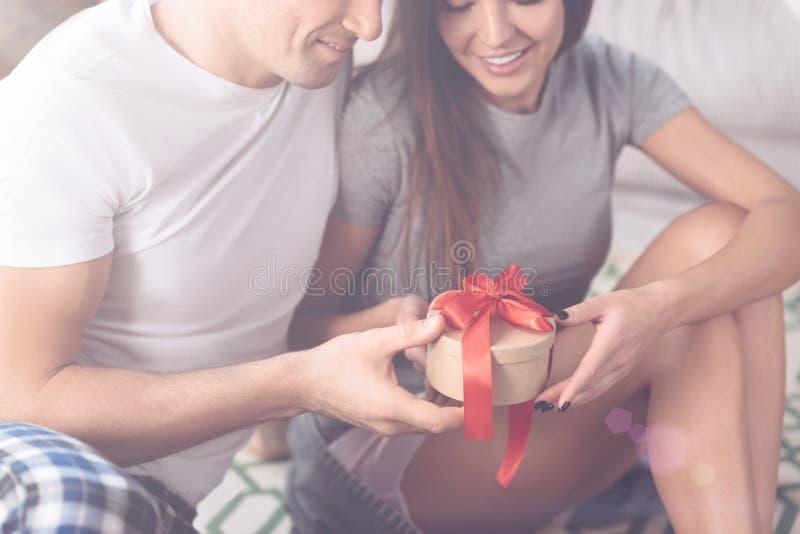 Fermez-vous du boîte-cadeau avec le ruban rouge étant dans des mains masculines photos stock