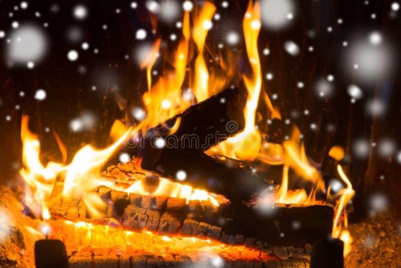 Fermez-vous du bois de chauffage brûlant dans la cheminée et la neige images stock