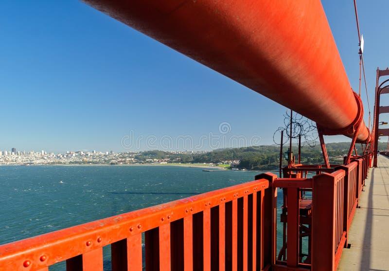 Fermez-vous du câble de golden gate bridge avec le centre ville comme fond image libre de droits