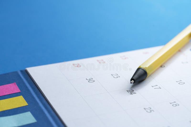 Fermez-vous du calendrier et du stylo sur le fond bleu images libres de droits