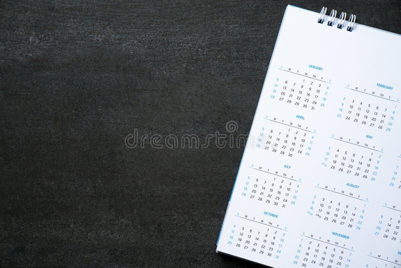 Fermez-vous du calendrier sur la table noire, en prévoyant pour le concept de planification de réunion d'affaires ou de voyage photos stock