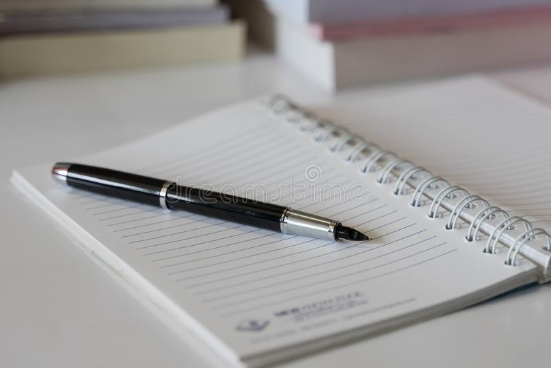Fermez-vous du carnet avec l'encre-stylo et des lunettes mises sur la table blanche avec le centre de tache floue des livres comm image libre de droits