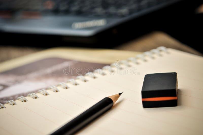 Fermez-vous du carnet avec le crayon et la gomme sur le dessus photo stock
