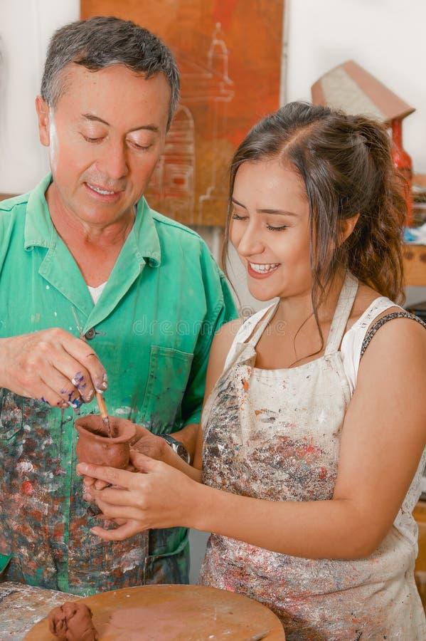 Fermez-vous du ceramist de femme et d'homme travaillant ensemble sur la sculpture sur la table en bois dans l'atelier photographie stock