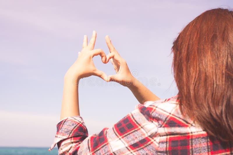 Fermez-vous du coeur fait par le fond de mains de femelle l'océan de turquoise images libres de droits