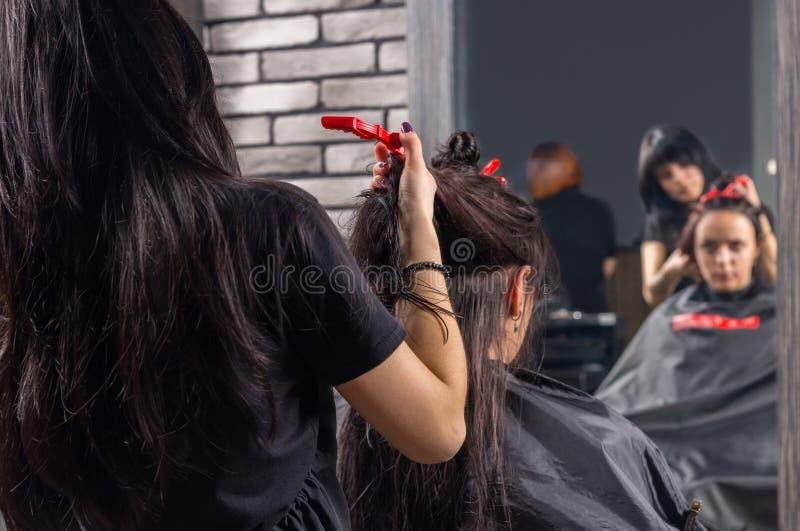 Fermez-vous du coiffeur féminin modelant les cheveux bruns du jeune bru photographie stock libre de droits