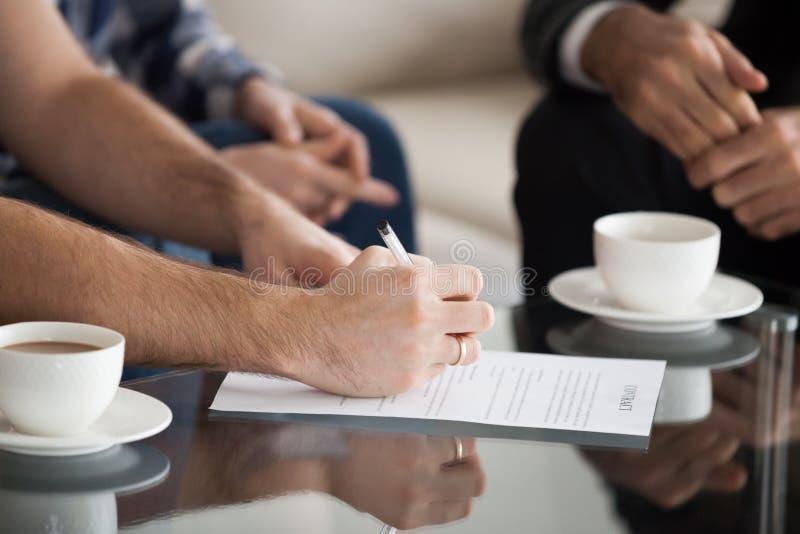 Fermez-vous du contrat de signature de mari avec l'épouse près photographie stock