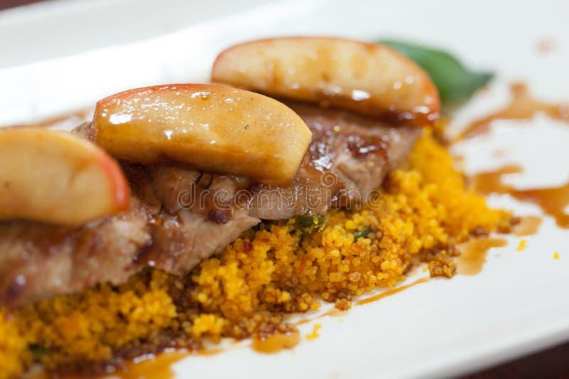 Fermez-vous du couscous avec de la viande garnie avec la pomme photos stock