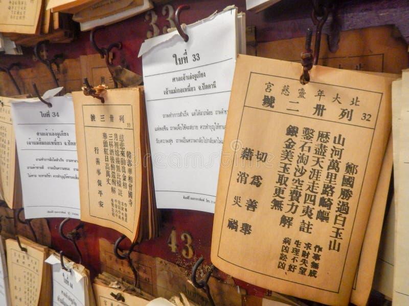Fermez-vous du diseur de bonne aventure que des papiers sticked sur le mur au tombeau en Thaïlande, thaïlandais et la langue chin images libres de droits