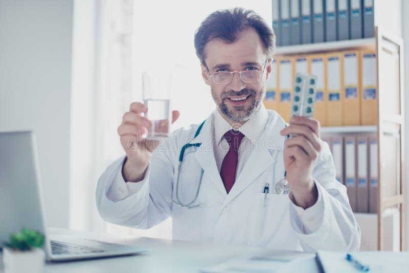 Fermez-vous du Doc. gai recommandant les pilules et le verre de wat photographie stock libre de droits