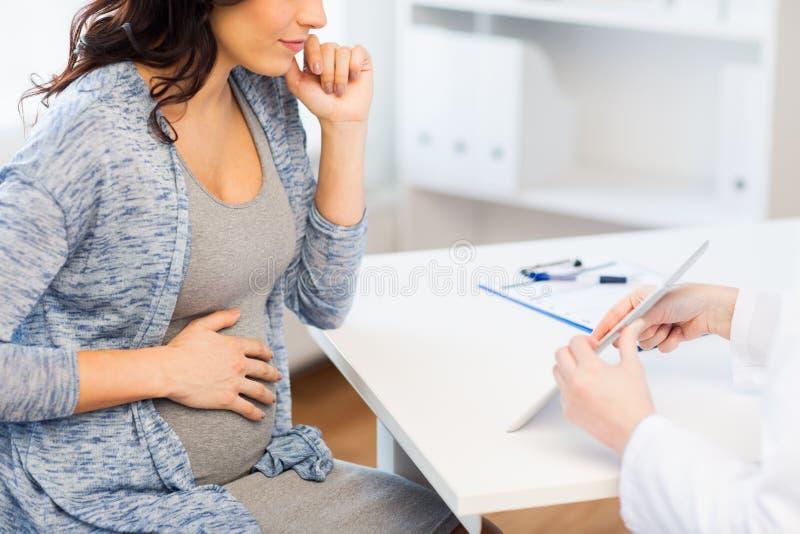 Fermez-vous du docteur avec le comprimé et la femme enceinte image stock