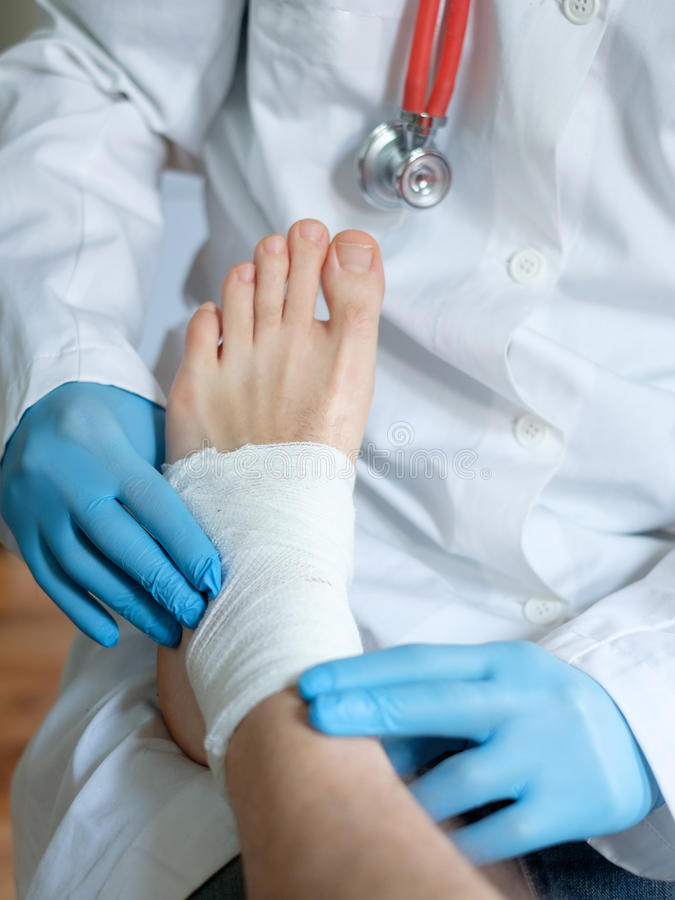 Fermez-vous du docteur bandant un blessé pied images stock