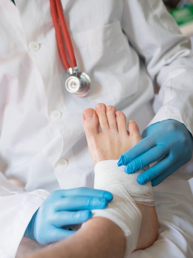 Fermez-vous du docteur bandant un blessé pied photos stock