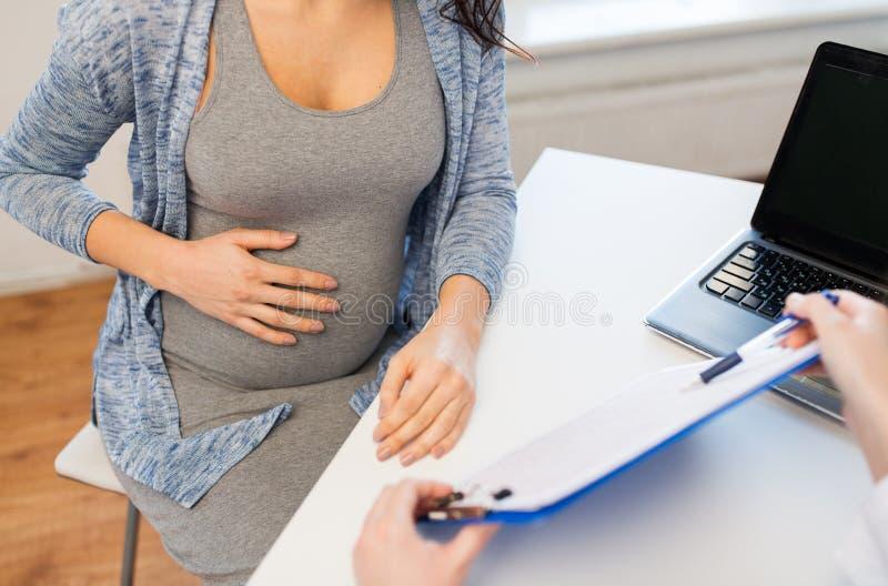 Fermez-vous du docteur et de la femme enceinte à l'hôpital image stock