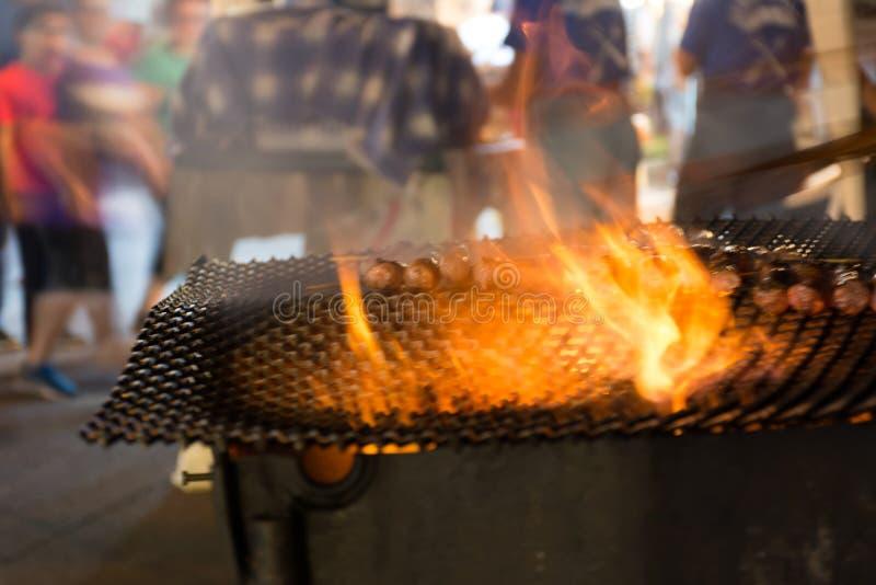Fermez-vous du feu faisant cuire des saucisses dans la rue pendant la célébration italienne image stock