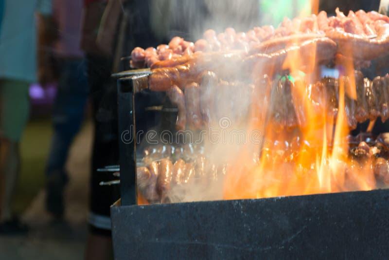 Fermez-vous du feu faisant cuire des saucisses dans la rue pendant la célébration italienne photo stock