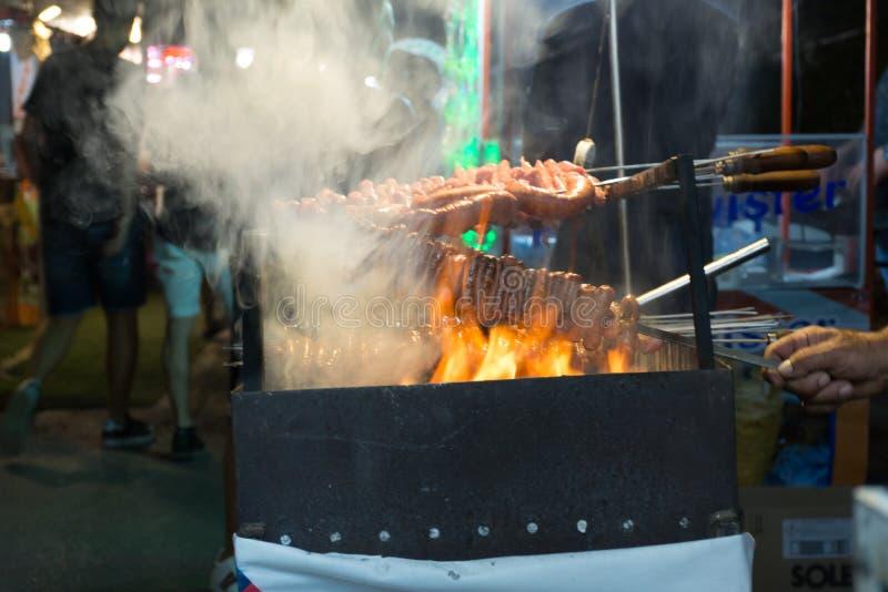 Fermez-vous du feu faisant cuire des saucisses dans la rue pendant la célébration italienne images libres de droits