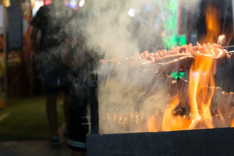 Fermez-vous du feu faisant cuire des saucisses dans la rue pendant la célébration italienne photographie stock