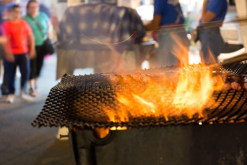 Fermez-vous du feu faisant cuire des saucisses dans la rue pendant la célébration italienne photographie stock libre de droits