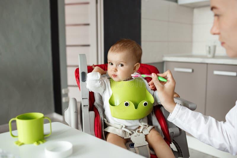 Fermez-vous du fils nouveau-né mignon s'asseyant dans la cuisine dans la chaise de bébé et la tête de rotation refusant de côté d image stock