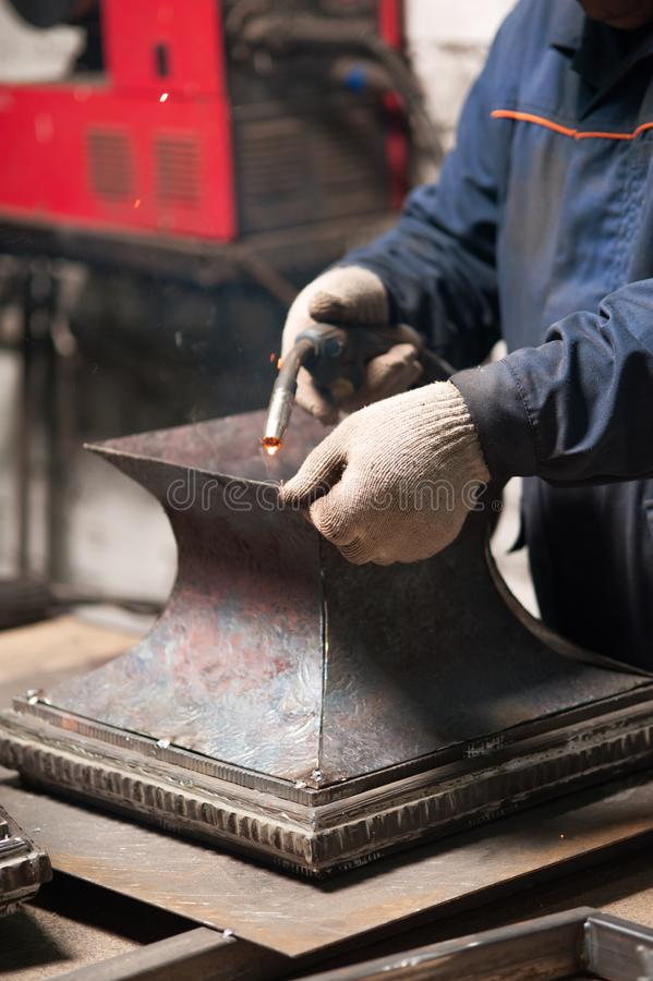 Fermez-vous du forgeron soudant une plaque de métal photographie stock libre de droits